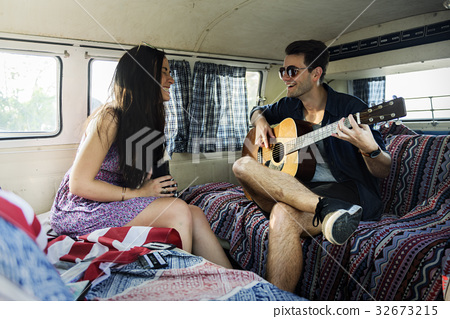 Man Playing Guitar with Lover in a Van Road Trip 32673215