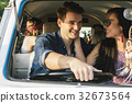 Couple Driving a Car Traveling on Road Trip with FriendsTogether 32673564