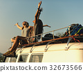 Women Sitting on The Roof of the Van Traveling Road Trip 32673566