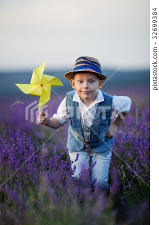 Happy fashion boy in lavender summer field with 32699384
