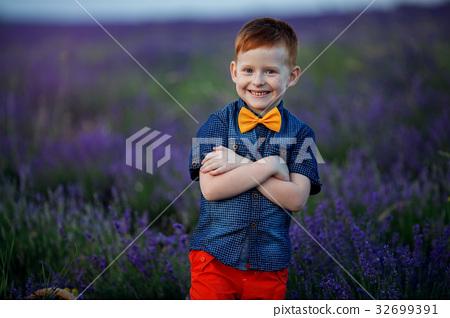 Happy fashion boy in lavender summer field with 32699391