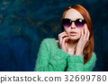 young beautiful redhead woman in sunglasses 32699780