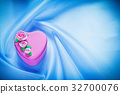 Pink decorated present box on blue fabric 32700076
