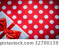 White gift box with knot on polka-dot red fabric 32700139
