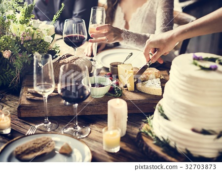 Bride and Groom Having Meal with Friends at Wedding Reception 32703873