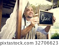 Man Hanging Open Sign by the Glass Window 32706623