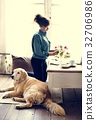 Woman Arranging Flowers with Goldent Retriever Dog Laying 32706986