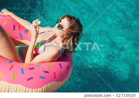 sexy girl in sunglasses eating ice cream in pool  32710020
