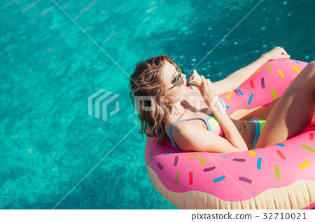 sexy girl in sunglasses eating ice cream in pool  32710021