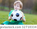 Little cute kid boy of 4 playing soccer with 32710334