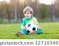 Little cute kid boy of 4 playing soccer with 32710340