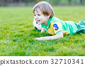 Little cute kid boy of 4 playing soccer with 32710341