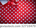 Opened gift box with bow on polka-dot red fabric 32710470