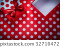Opened present box on polka-dot red tablecloth 32710472