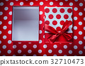 Opened present box on polka-dot red fabric 32710473