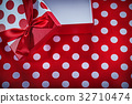 Opened present box with bow on polka-dot red 32710474