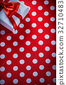 Packed gift box on polka-dot red fabric holidays 32710483