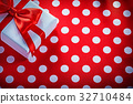 Packed present box on polka-dot red fabric 32710484