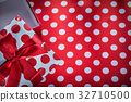 Present box with bow on polka-dot red textile 32710500