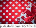 Wrapped gift box with bow on polka-dot red table 32710510