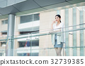 The lady is standing on balcony and putting right hand near her chin 32739385