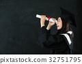 young happy grad looking through diploma 32751795
