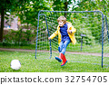 Active cute little kid boy playing soccer and 32754705