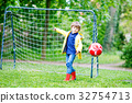 Active cute little kid boy playing soccer and 32754713