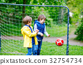 Two active kids boys playing soccer and football 32754734