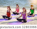 Group of young people practicing yoga on the beach 32803066