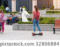 Young woman riding a hoverboard on the city square 32806884
