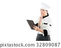 chef looking at digital pad and thinking 32809087