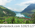 A village by the lake in the background of the  mountains 32825127