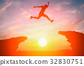 Silhouette man jump over cliff obstacle in sunset 32830751