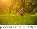 Girl doing yoga asana cat pose wirh leg grip. 32832674