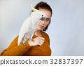 Two bird, cute parrots, sit on woman. Studio shoot 32837397