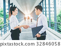 Business partnership handshaking after striking  32846058