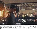 Young man exercises by lifting iron balls  32852156
