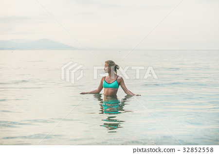Young woman in blue swimsuit standing in sea in 32852558
