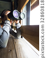 Woman looking though binoculars at wooden house 32860818