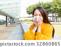 Sick young woman blowing her nose 32860865