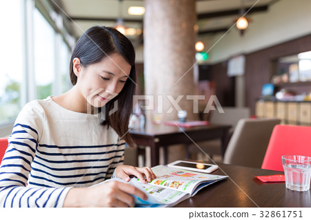 Woman reading magazine in coffee shop 32861751