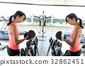 Sport Woman practices weight lifting of the dumbbell in gym 32862451
