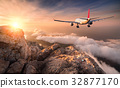 Airplane is flying over clouds at sunset 32877170