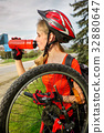 Bicycle tire pumping by child bicyclist. Girl 32880647