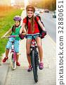 Girls children cycling on yellow bike lane. There 32880651