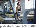 The woman is holding the phone and listening to music in gym club. 32886409