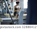 The woman is sitting and using the phone in fitness club. 32886412
