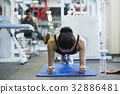 A woman is doing a plank at a sporting club 32886481