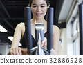 young girl is listening to music while exercising on cycling machine 32886528